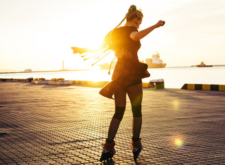 Young stylish funky girl with green hair riding roller skates and dancing near sea port during sunset