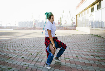 Attractive young woman in a stylish look and green hair dancing freely on urban background