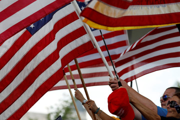 Activists wave flags during the Mother of All Rallies demonstration promoting on the National Mall in Washington