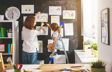 Mother and child girl hang their drawings on wall