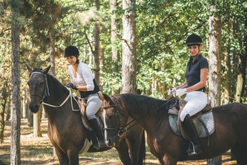 Two young women riding horses in nature