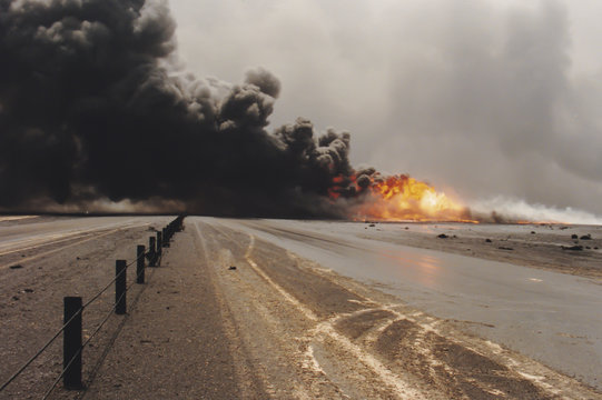 Road through oil well burning in field with oil slick, Kuwait