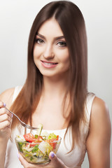 Diet. Healthy food. Weight loss and subtle body concepts. Fitness girl who has a bowl of salad. Conception of health and beauty. On a gray background