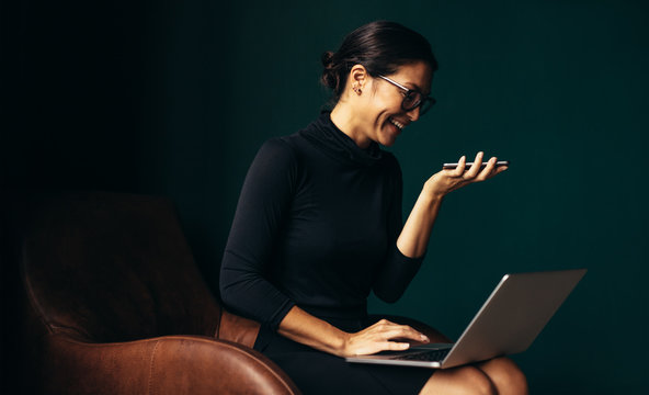 Smiling woman using laptop and holding smartphone