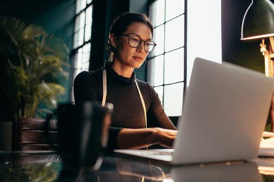 Female fashion designer working on laptop in studio