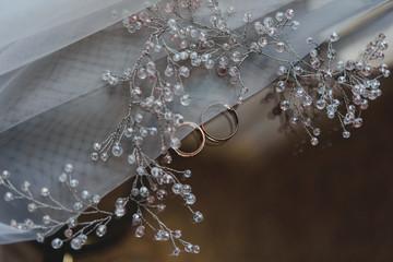 Два золотых обручальных кольца и свадебный аксессуар невесты на стеклянном фоне