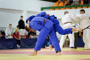 Two judokas in blue judo kimonos fighting