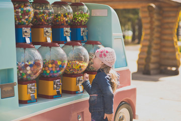 The little girl stopped in front of a battery of machines for the sale of small sweets. Genuinely enjoys opportunities to choose any treat Portrait of a girl in the Park on a walk.