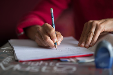 Hand writing on paper with pencil on desk. Selective focus on pencil, home interior, very shallow depth of field.