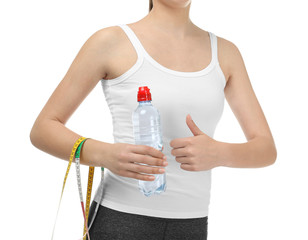 Young woman with measuring tape and bottle of water on white background. Diet concept