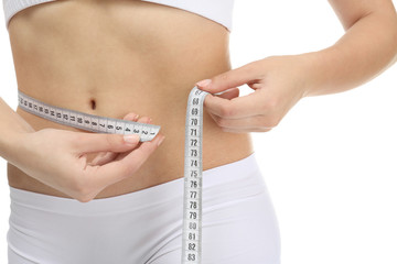 Young woman in underwear with measuring tape on white background, closeup. Diet concept