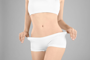 Young woman in underwear on gray background. Diet concept