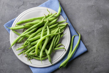 Plate with fresh green beans on grey background