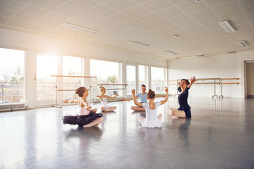Group of little ballerinas with hands up in class