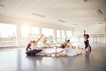 Group of children dancing ballet doing leg split