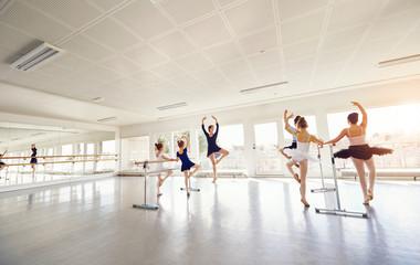 Woman showing ballet dance to children in class