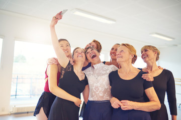 Group of laughing women taking selfies in a dance studio