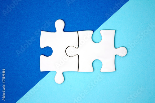 two puzzle pieces connect on blue geometry color paper minimal