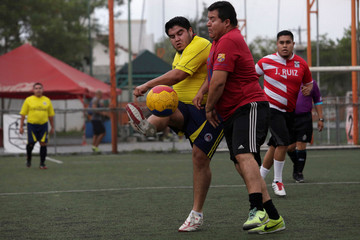 "Players fight for the ball during their ""Futbol de Peso"" (Soccer of Weight ) league soccer match, a league for obese men who want to improve their health through soccer and nutritional counseling, in San Nicolas de los Garza"