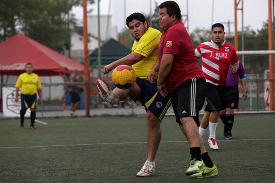 """Players fight for the ball during their """"Futbol de Peso"""" (Soccer of Weight ) league soccer match, a league for obese men who want to improve their health through soccer and nutritional counseling, in San Nicolas de los Garza"""