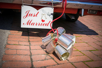 Just Married Cans attached to the back of a old timer car to celebrate a wedding