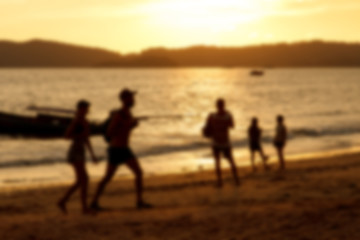 Blurred background of silhouette couple on beach when sunset tine