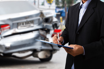 Car insurance agents writing clipboard as a proof of insurance claim for car accident damaged