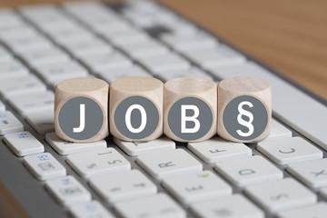 """Würfel mit dem Wort """"Job"""" und Paragraphensymbol auf Tastatur"""