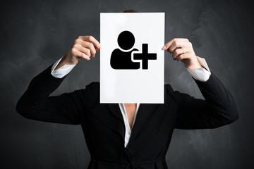 """Geschäftsfrau hält Schild mit einem """"Mitarbeiter hinzufügen""""-Symbol vor ihrem Gesicht"""