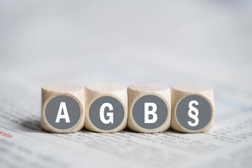 """Würfel mit Aufschrift """"AGB"""" und Paragraphensymbol auf einer Tageszeitung"""