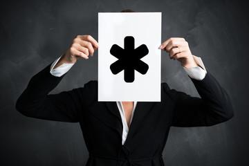 Geschäftsfrau hält Schild mit einem Sternchen-Symbol vor ihrem Gesicht