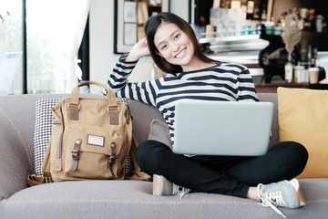 Beautiful asian girl using laptop computer while sitting on sofa with smiling face emotion, people and technology concept, lifestyle