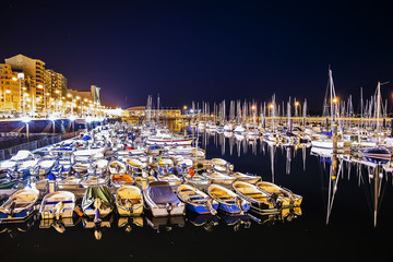Pier with many moored boats in the port at night