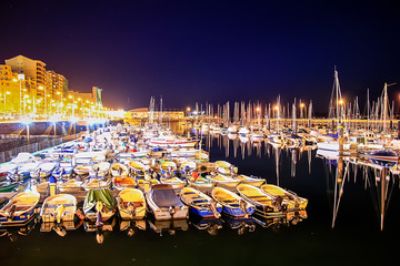 SANTANDER, SPAIN - February 20, 2017: Pier with many moored boats in the port at night