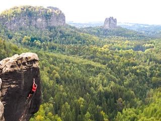 Deutschland, Sachsen, Lohmen, Sächsische Schweiz, Kletterer am Felsen, im Hintergrund Falkenstein