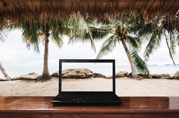 Laptop computer on wooden table with at the beach