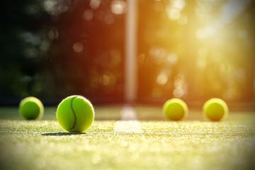 Tennis balls on grass court with sunlight