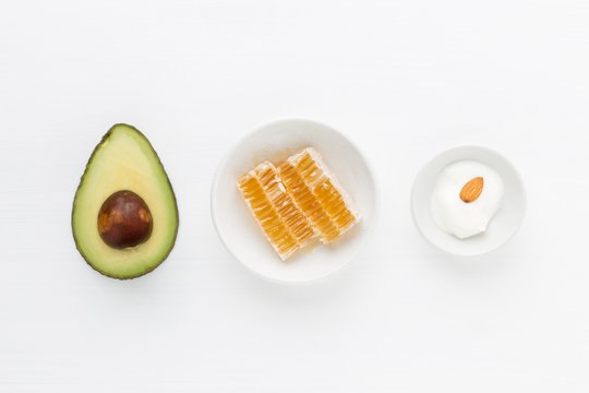 Homemade skincare body scrub with fresh avocado, honey, yogurt and almond on white background.
