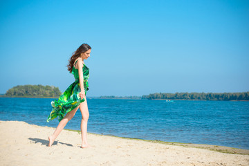 Woman wearing in green dress rest on a beach at warm day.  Mature thin lady Outdoors  on beach sand near water Landscape. Attractive Middle Aged Woman rest on nature