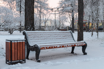 In the city park bench covered with snow.