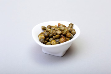 bowl with fresh capers isolated on white background.