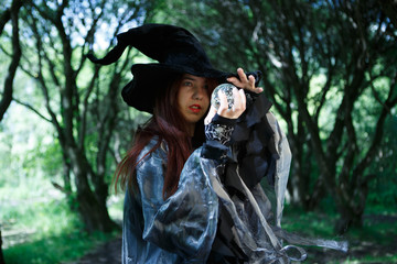 Witch in black hat holds magic ball
