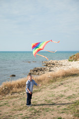 little kid holds a kite flying standing on the beach against the sea and sky