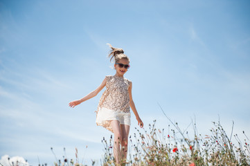 happy young girl refreshed by the wind walking among field of flowers on blue sky background