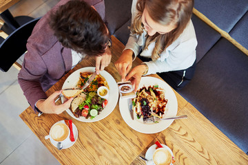 Cute young couple eating together and taking photos of their food in a restaurant