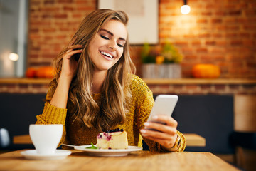 Smiling beautiful young woman looking at phone while enjoying cake and coffee in a cafeteria