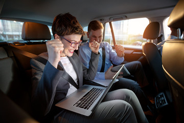 Excited businesspeople looking at laptop in car on trip.