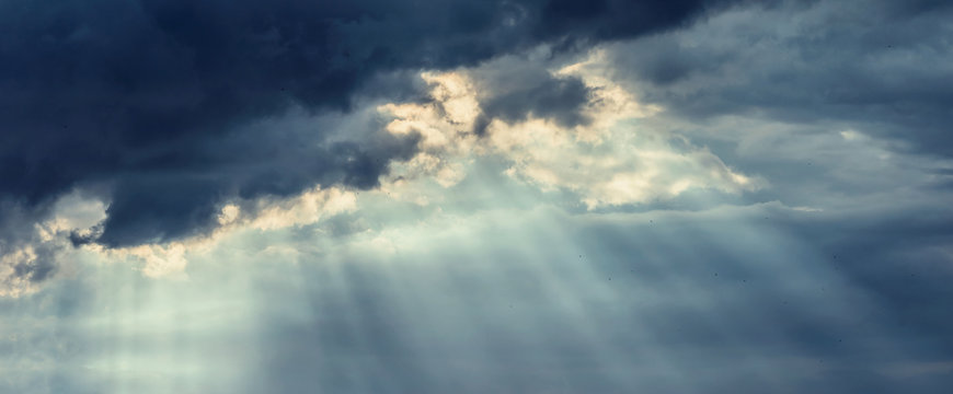 Beautiful dark storm cloudy sky with rays of the sun breaking through the clouds