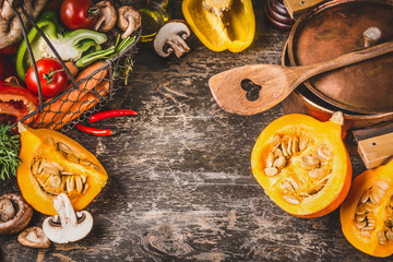 Pumpkin on kitchen table background with wooden cooking spoon, pot and vegetables, top view, place for text.  Healthy Vegetarian Food and Eating