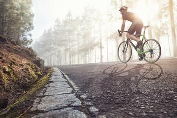 Fahrradfahrer auf einer Straße im nebligen Wald